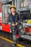 在消防局的微笑的消防员支持的卡车 免版税库存图片