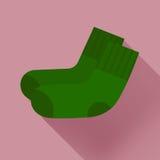 在淡粉红的背景的深绿袜子 库存图片