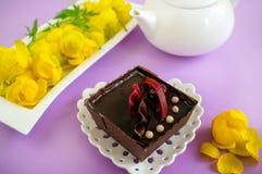 在淡紫色背景的自创蛋糕在与一个白色水壶的茶服务 免版税库存图片