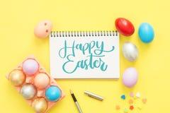 在淡色构成和在笔记本的文本愉快的复活节天绘的平的位置顶视图五颜六色的复活节彩蛋有画笔的 图库摄影