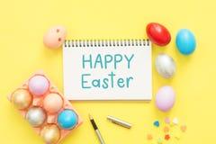 在淡色构成和在笔记本的文本愉快的复活节天绘的平的位置顶视图五颜六色的复活节彩蛋 免版税库存照片