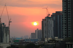 在淡色橙色天空的太阳设置在建造场所中,曼谷的运转的起重机 免版税图库摄影