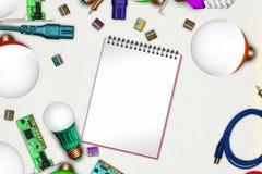 在淡色纸的工程学概念与被打开的笔记本页和被带领的电灯泡,焊铁, pcb,电灯泡,绝缘胶带 库存照片