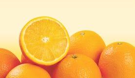 在淡黄色的切的和整个桔子 库存图片