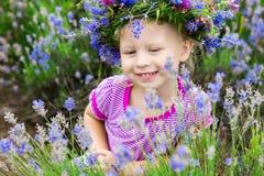 在淡紫色中花的俏丽的女孩  库存图片