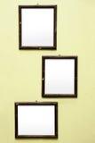 在淡黄色墙壁上的三个老土气空白的框架 免版税库存图片