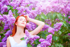 在淡紫色树附近的女孩 免版税库存照片
