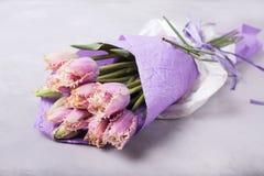 在淡紫色纸包裹的淡紫色郁金香花束  与五颜六色的郁金香的静物画 新鲜的春天郁金香 安置文本 花conce 库存图片