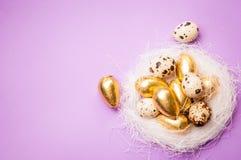 在淡紫色背景的复活节金黄鸡蛋 图库摄影