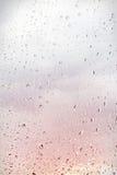 在淡紫色背景的雨下落 图库摄影