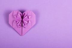 在淡紫色背景的紫色华伦泰origami 纸张的重点 惊奇在华伦泰` s天 库存照片