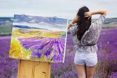 在淡紫色领域的年轻艺术家绘画 免版税库存图片