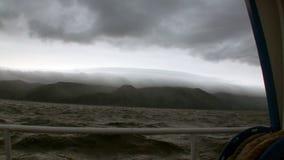 在深灰云彩背景的游艇在贝加尔湖的路轨在天空的和风暴 影视素材