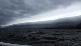 在深灰云彩背景的游艇在贝加尔湖的路轨在天空的和风暴 股票录像