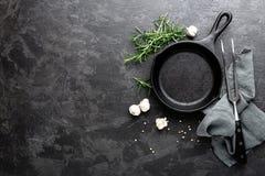 在深灰烹饪背景,看法的空的生铁煎锅从上面 免版税库存照片