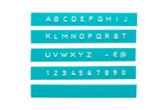 在深蓝塑料磁带上的压印的字母表 库存照片