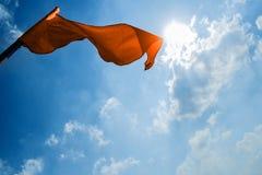 在深蓝天空的背景的红旗与云彩的 免版税库存图片