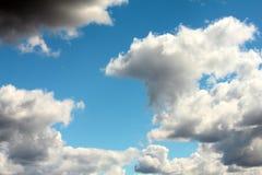 在深蓝天空背景的白色云彩  免版税库存图片