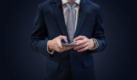 在深蓝套装的商人使用流动巧妙的电话,在蓝色背景 库存照片