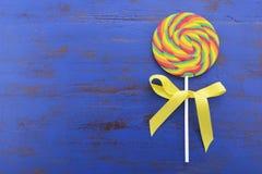 在深蓝木桌上的明亮的彩虹棒棒糖糖果 图库摄影