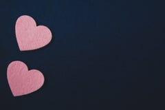 在深蓝毛毡背景的桃红色心脏 库存图片