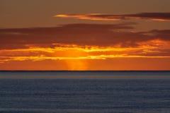 在深蓝海洋水的风景五颜六色的日出 免版税库存照片