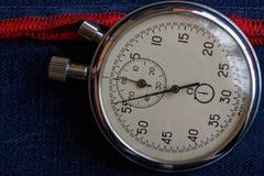 在深蓝牛仔布背景的秒表与红色小条、价值措施时间、老时钟箭头分钟和第二准确性定时器recor 免版税库存图片