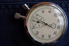 在深蓝牛仔裤背景,价值措施时间、老时钟箭头分钟和第二个准确性定时器纪录的秒表 库存图片