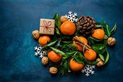 在深蓝背景的明亮的蜜桔绿色叶子杉木锥体礼物盒雪剥落装饰品 圣诞节 免版税库存照片