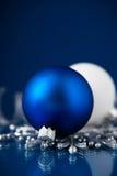 在深蓝背景的银色和蓝色圣诞节装饰品 圣诞快乐看板卡 免版税库存图片