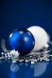 在深蓝背景的银色和蓝色圣诞节装饰品 圣诞快乐看板卡 免版税库存照片