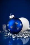 在深蓝背景的银,白色和蓝色圣诞节装饰品 圣诞快乐看板卡 免版税库存照片