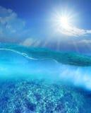 在深蓝色发光在天空的海水和太阳下的珊瑚礁 图库摄影