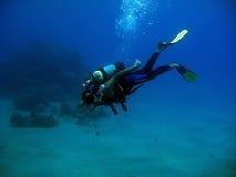 在深蓝色的佩戴水肺的潜水 图库摄影
