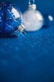 在深蓝闪烁背景的白色和蓝色圣诞节装饰品与文本的空间 库存图片