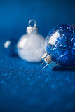 在深蓝闪烁背景的白色和蓝色圣诞节装饰品与文本的空间 免版税库存照片