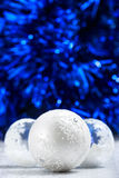 在深蓝bokeh背景的白色和银色圣诞节球与文本的空间 库存图片