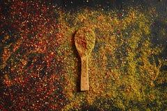 在深黑色背景的被分类的香料 食物的调味料 咖喱,辣椒粉,胡椒,豆蔻果实,姜黄 顶视图 免版税库存照片