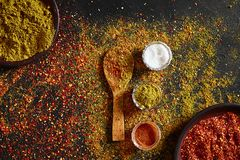 在深黑色背景的被分类的香料 食物的调味料 咖喱,辣椒粉,胡椒,豆蔻果实,姜黄 顶视图 库存照片