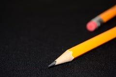 在深黑色被弄脏的背景的两支黄色铅笔 文教用品 办公室工具 到达天空的企业概念金黄回归键所有权 免版税库存图片