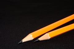 在深黑色被弄脏的背景的两支黄色铅笔 文教用品 办公室工具 到达天空的企业概念金黄回归键所有权 免版税库存照片