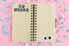 在混乱的中心从文具的是在春天的一个笔记本 在棕色页的题字我的想法 库存图片