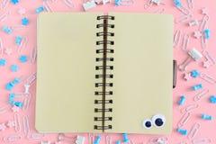 在混乱的中心从文具的是在春天的一个笔记本 空的棕色页 在桃红色的明亮的照片 免版税库存图片