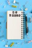 在混乱的文具在蓝色背景 在中心谎言在春天的一个开放笔记本有白页的 我的目标 库存照片