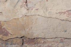 在混凝土墙上的老切削的膏药,切削的油漆,米黄纹理,背景 库存图片