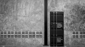 在混凝土墙上的闭合的铁门有通风设备的,黑白场面 免版税库存图片