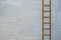 在混凝土墙上的黄色固定的梯子 库存图片