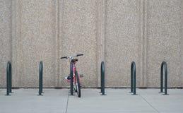 在混凝土墙前面的自行车机架 库存图片