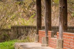 在混凝土墙后的老被盖的亭子 免版税库存图片