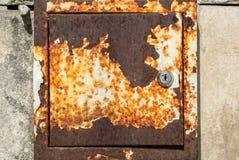 在混凝土墙纹理背景的老生锈的金属箱子 库存图片